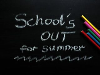 School`s out for summer text and colored pencils on chalkboard
