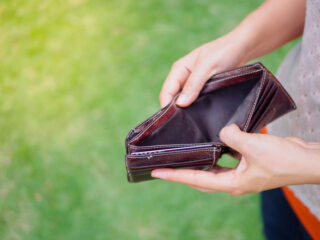 Unhappy bankrupt woman with empty wallet. Young woman shows her empty wallet. Bankruptcy